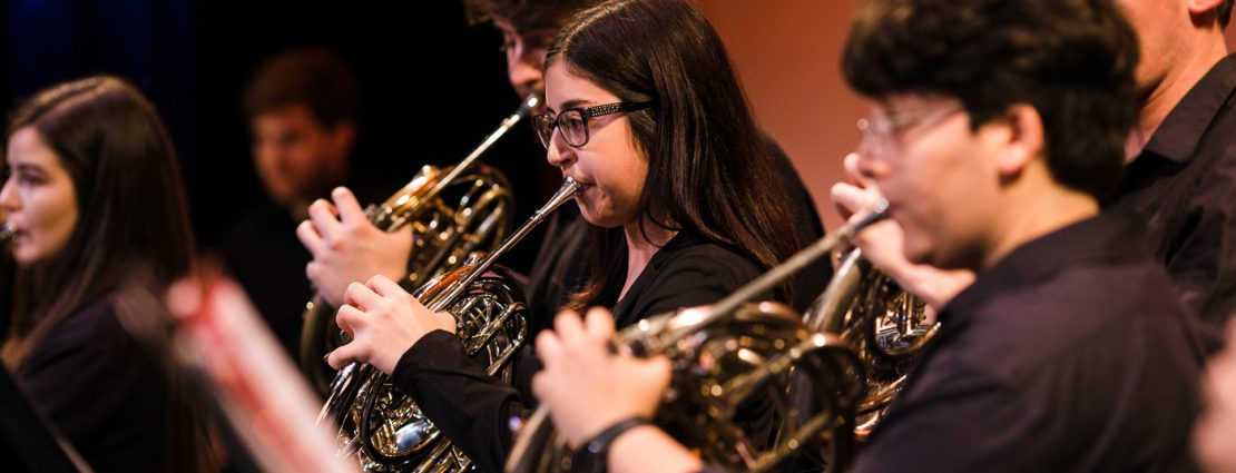 Student play the horn during a brass ensemble concert.